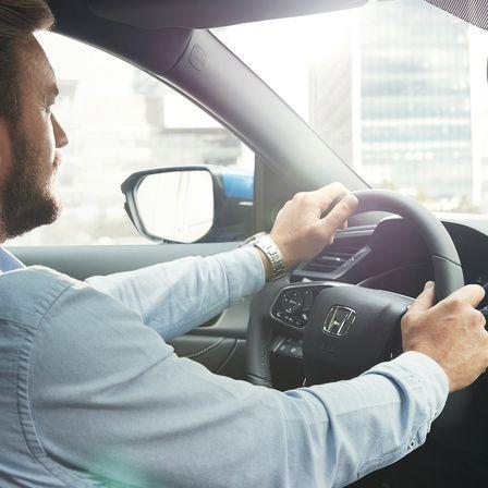 Steering wheel of Honda Civic five-door and driver.