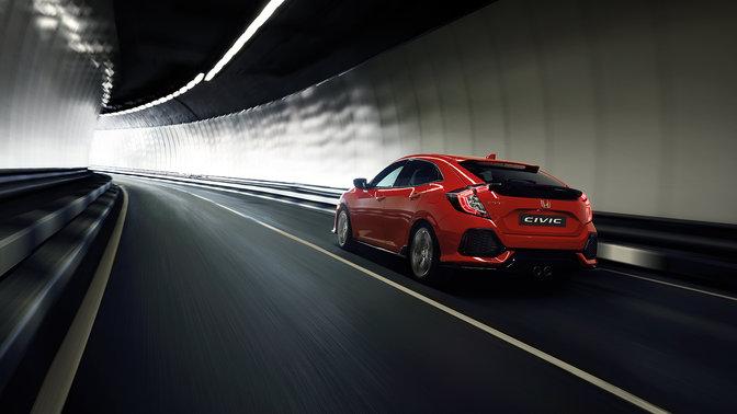 Driekwart achteraanzicht van Honda Civic die door tunnel rijdt.