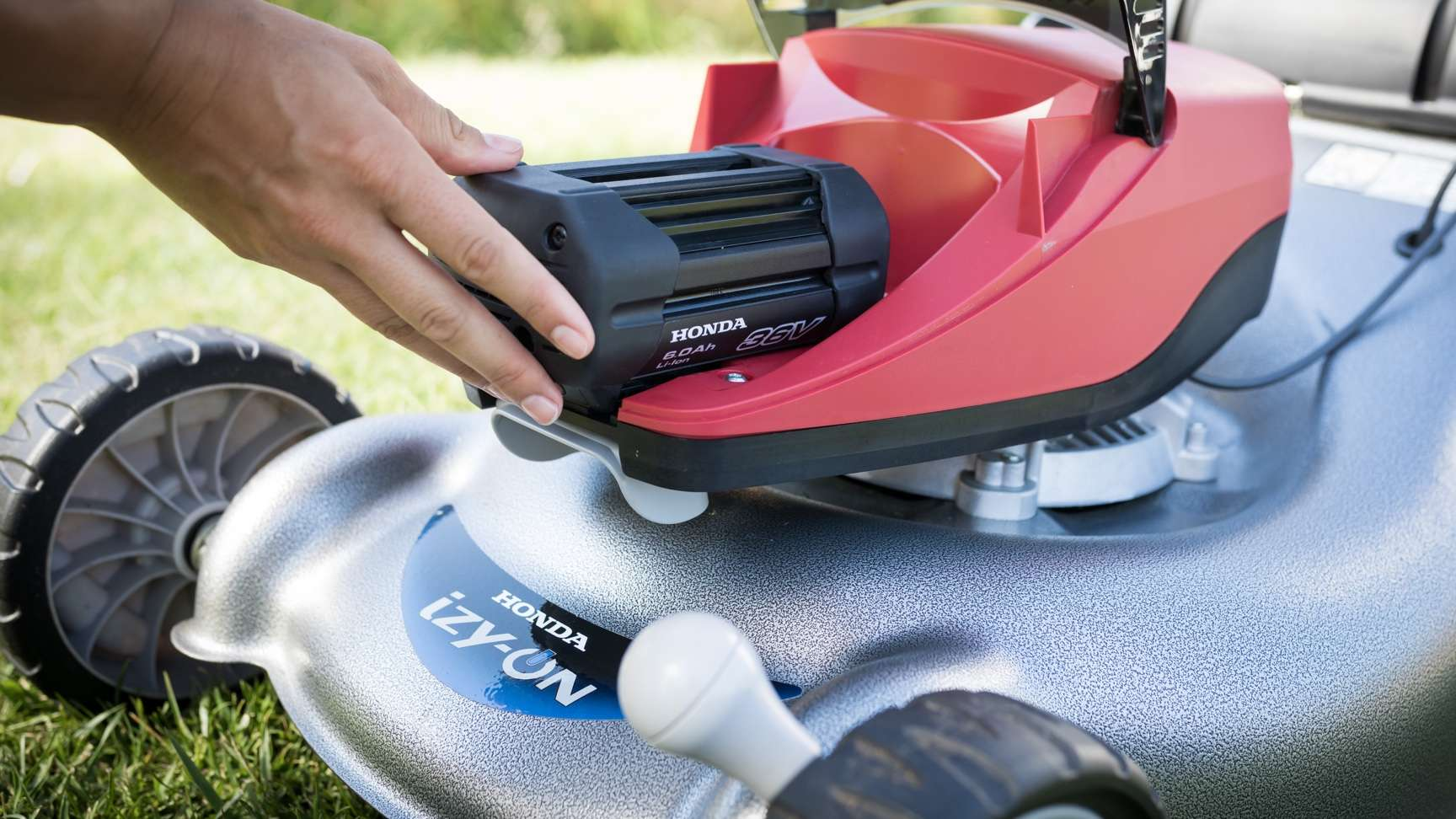 Model hands changing battery of Honda izy-ON mower.