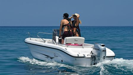 Boat using Honda engine, being used by models, coastal location.