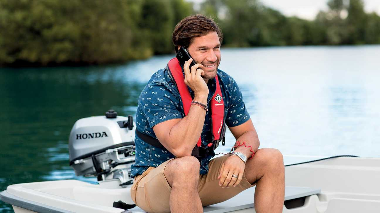 Man on small boat charging his phone off of his Honda Outboard engine while talking